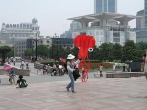 A street vendor holding a bright red kite